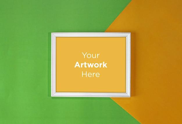 黄色と緑の紙の背景の空のフォトフレームモックアップデザイン