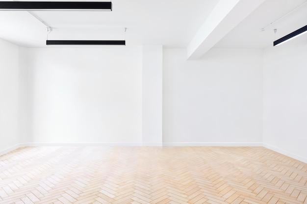 Scena di una stanza vuota con pareti bianche e pavimenti in parquet