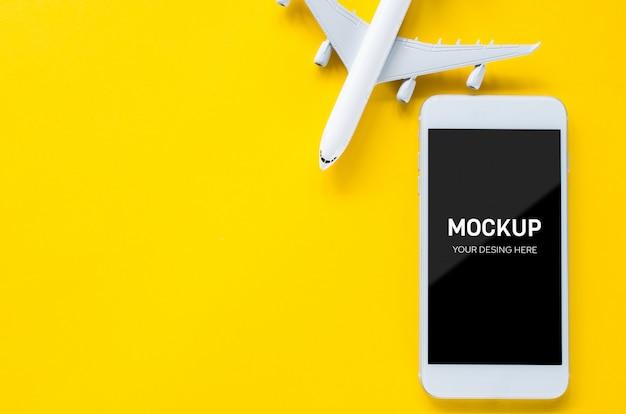 空の画面のスマートフォンと装飾的な飛行機、アプリのプレゼンテーション用のテンプレート。夏の旅行計画。