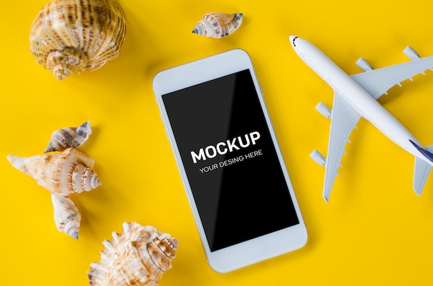 Empty screen smartphone, decorative airplane and seashells, template for app presentation.