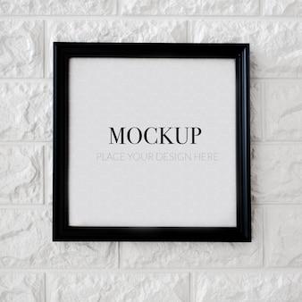 Пустая квадратная рамка для макета на кирпичной стене