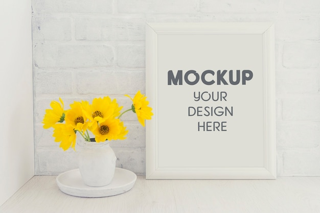 Empty white frame mockup with a bouquet of yellow sunflower flowers in a vintage vase