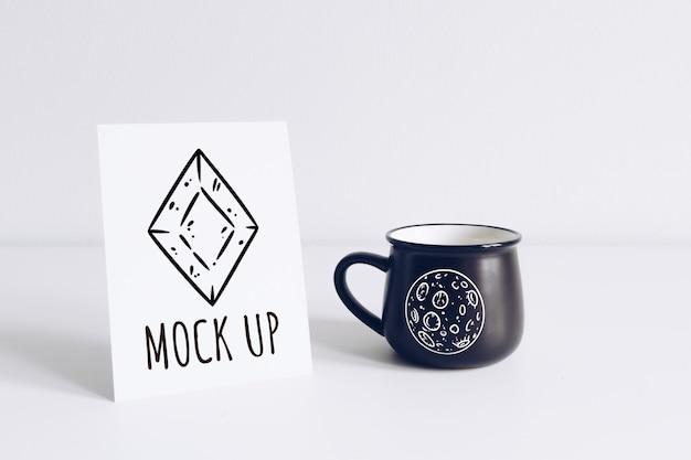 Enamel black mug and vertical postcard