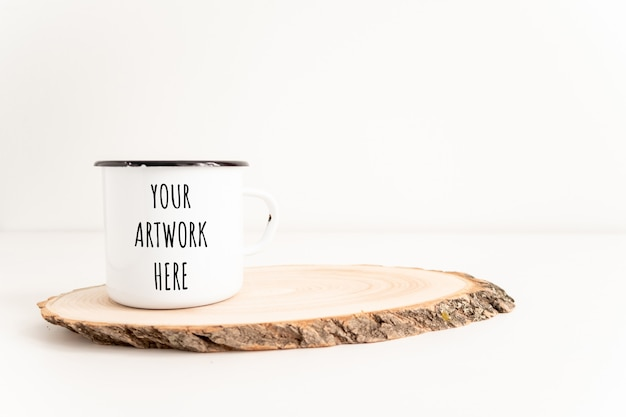 Enamel mug mockup with wooden cut tree section on white table. boho design of tin cup
