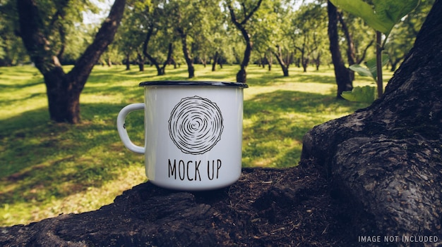 Enamel white mug on apple tree branch mockup