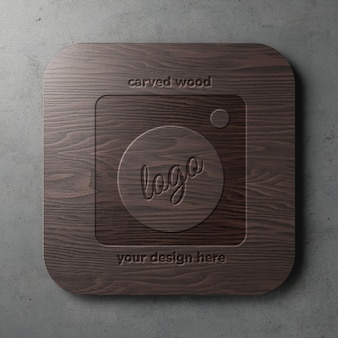 Engraved on rounded square dark wood logo mockup template in grunge wall front view