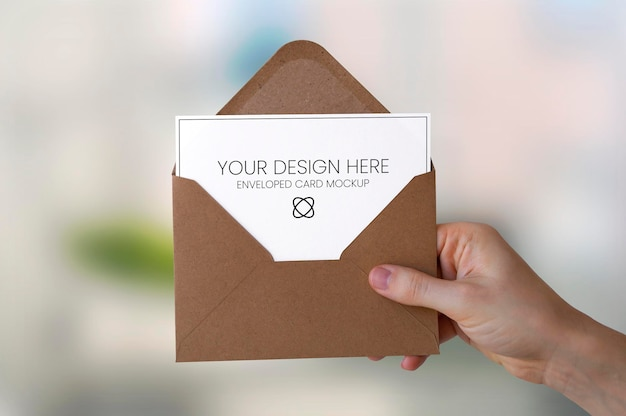 Enveloped paper holded by hand mockup