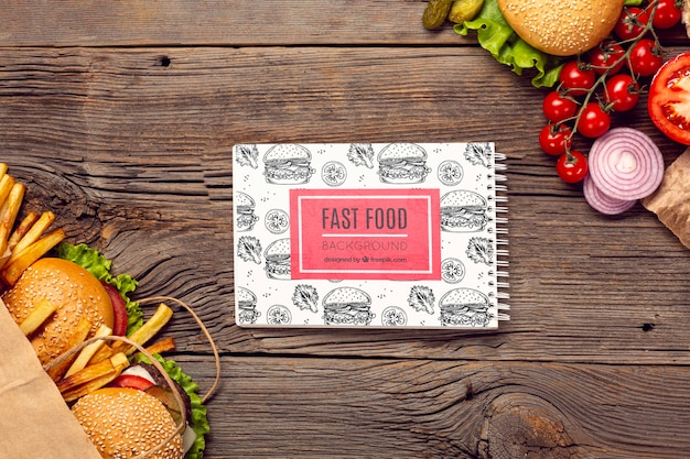 Fast food and veggies on wooden background