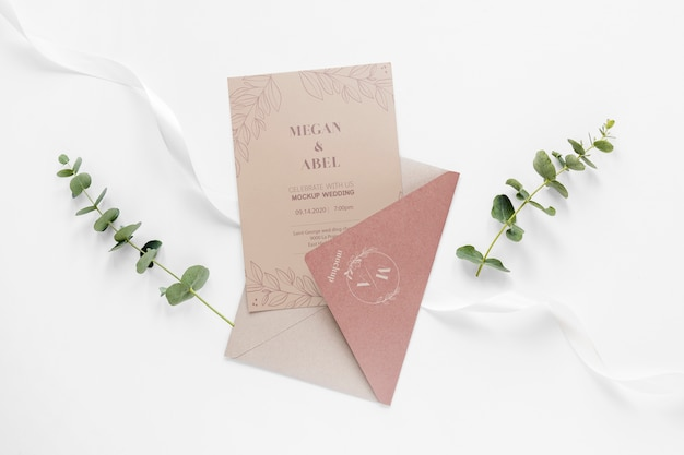 Fat lay of wedding card with envelope and plants