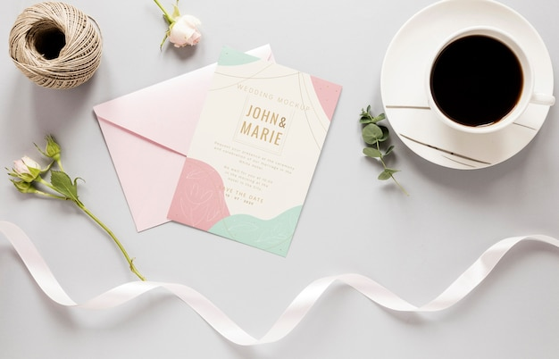 Fat lay of wedding card with ribbon and coffee
