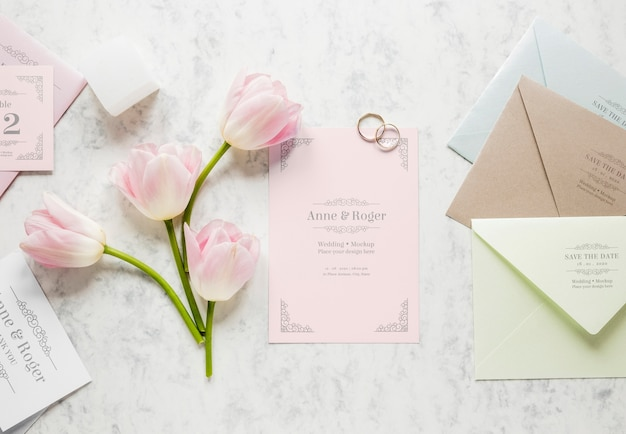Fat lay of wedding card with wedding rings and tulips