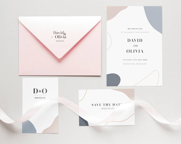 Fat lay of wedding cards with envelope and ribbon