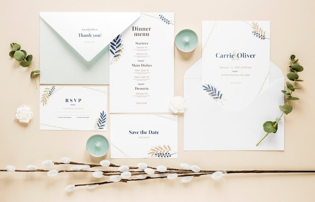 Fat lay of wedding cards with plants and candles
