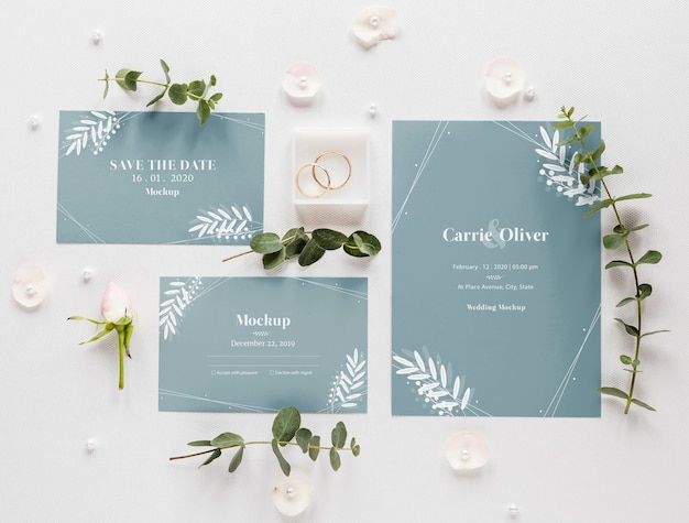 Fat lay of wedding cards with plants and rings