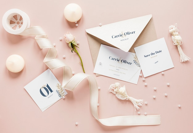 Fat lay of wedding cards with ribbon and candles
