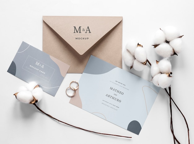 Fat lay of wedding cards with rings and cotton
