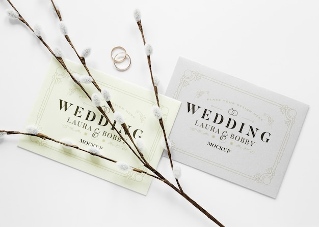 Fat lay of wedding cards with rings and flowers