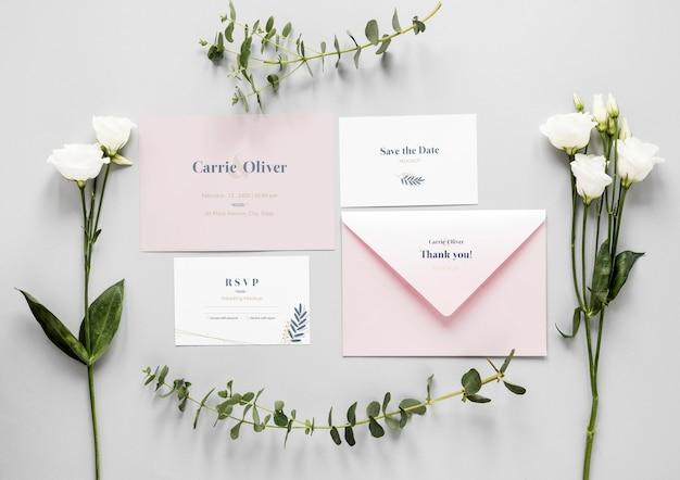 Fat lay of wedding cards with roses and plants