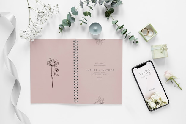 Fat lay of wedding notebook with smartphone and plants