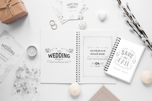 Fat lay of wedding notebooks with gift and candles