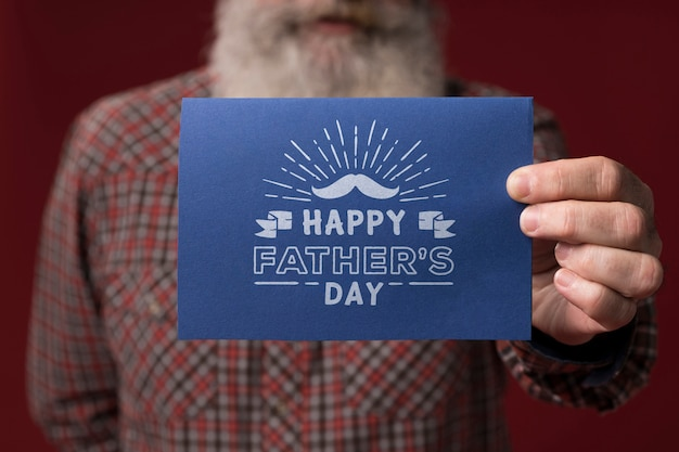 Father holding cardboard mock-up on burgundy background