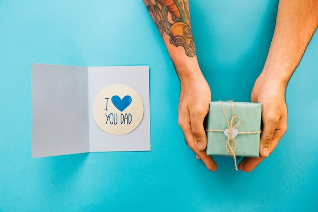 Fathers day mockup with card and hands holding present box