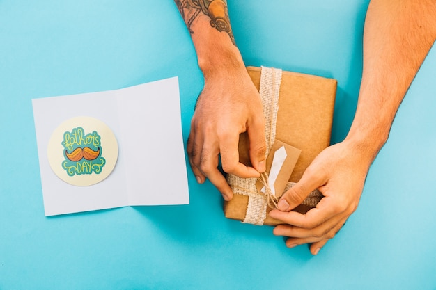 Fathers day mockup with card and hands preparing present box