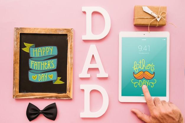 Mockup di giorno di padri con ardesia e tablet