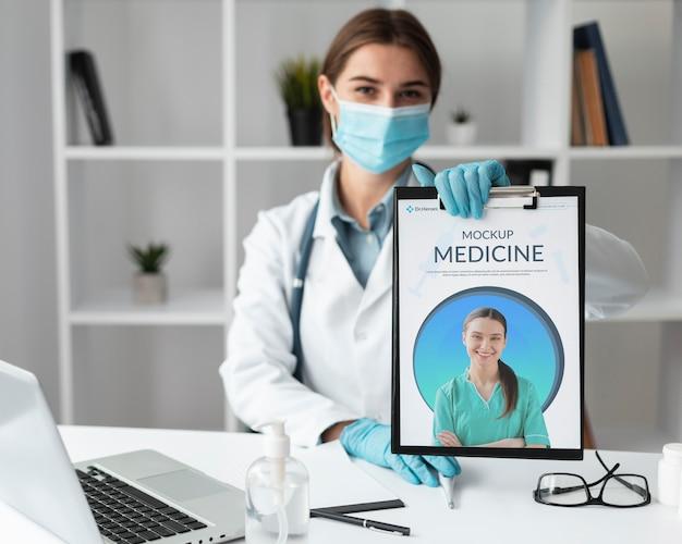 모형 클립 보드를 들고 여성 의사