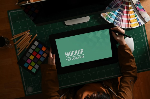 Female graphic designer working with mock up tablet and designer supplies on computer desk