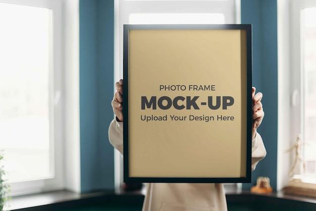 Female hand hold photo frame mockup indoor home