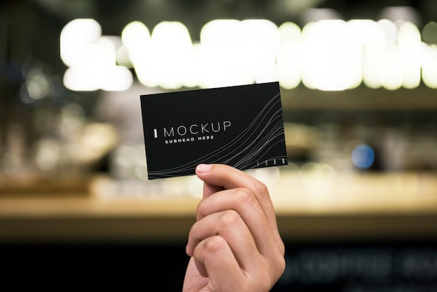 Female hand holding a black business card mockup