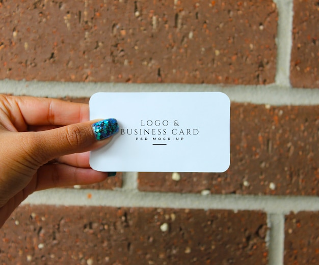 Female hand holding a business card