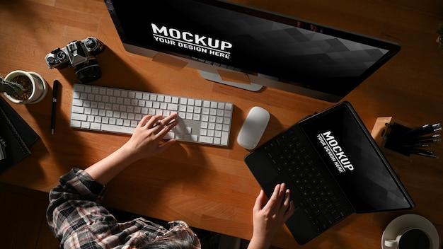 Женская рука работает с макетом компьютера и ноутбука