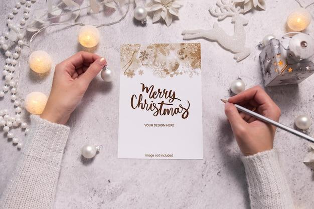 여성의 손은 크리스마스 엽서나 위시리스트를 씁니다. 크리스마스 기간 동안 축제 분위기