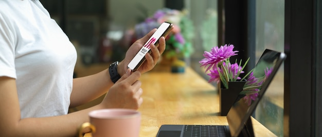 Female holding mockup smartphone while sitting at bar in cafe