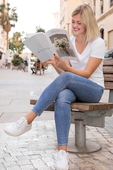 Female on street reading book Free Psd