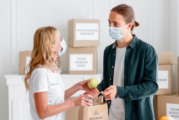 Женщина-волонтер с медицинской маской раздает пожертвование еды мужчине