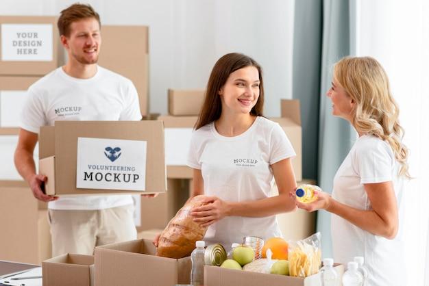Волонтеры-женщины готовят коробки для пожертвований с едой