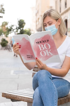 Femmina con maschera sul libro di lettura di strada