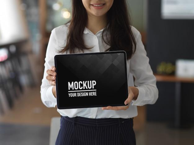 Работница показывает экран планшета макета, стоя в офисной комнате