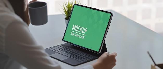 デジタルタブレットのモックアップで働く女性
