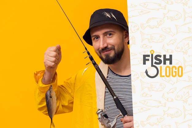 Fisherman in raincoat holding a fish
