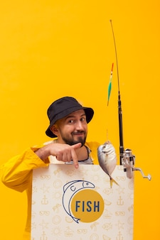 Fisherman in raincoat holding rod with fish
