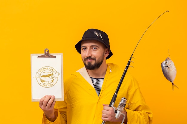 Pescatore in impermeabile con pesce trofeo in canna