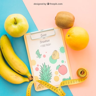 Fitness mockup with clipboard and fruits