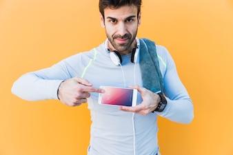 スマートフォンを見せる男とフィットネスモックアップ