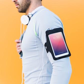 Фитнес-макет с человеком со смартфоном на руке