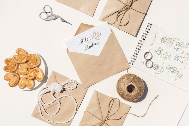 Flat lay arrangement of brown paper envelopes and wedding rings