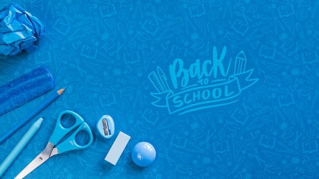 Flat lay arrangement with blue school supplies